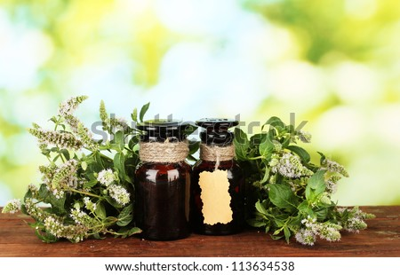 Essential oil and mint on green background close-up - stock photo