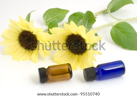 Essential oil and sunflower on white background - stock photo