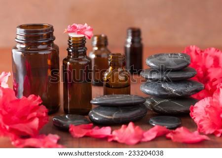 essential oil azalea flowers black massage stones - stock photo