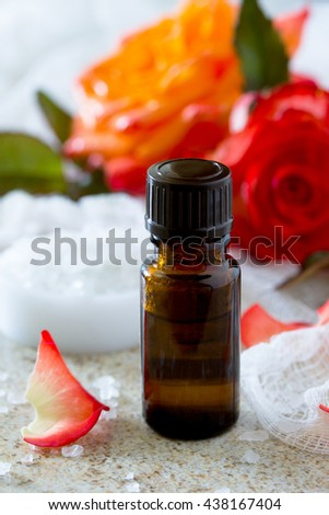 essential oil bottle of aromatherapy on a brown stone background. Rose Spa. - stock photo