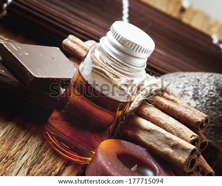 Essential Oil Bottle with Cinnamon Sticks and Chocolate.Aromatherapy Settlement - stock photo