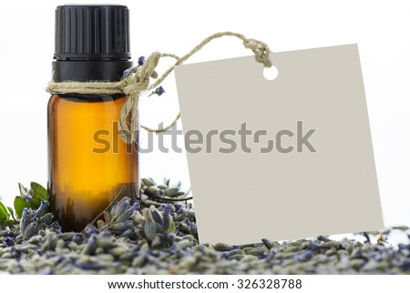 Essential oil, empty tag and lavander flowers on isolated background - stock photo