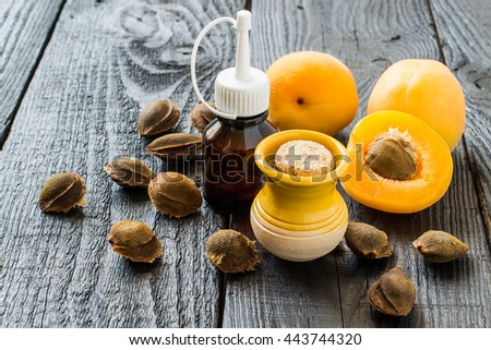 Essential oil from apricot kernels in small brown bottles and small yellow clay jar, fresh apricots and apricot seeds on a dark wooden table