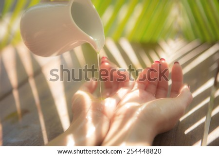 Essential oil in jug pouring on female hands in spa - stock photo