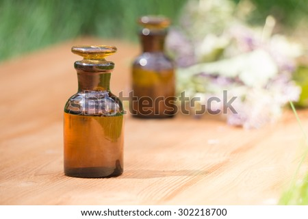 essential oil in little bottle and medical flowers herbs on wooden board - stock photo
