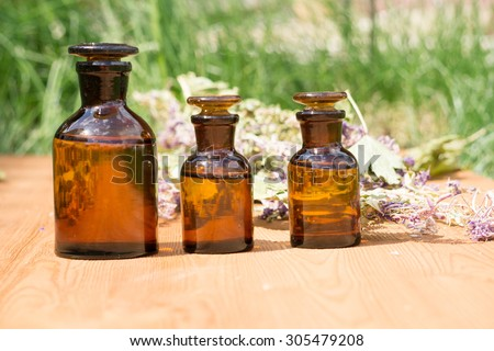 essential oil in little bottle and medical flowers herbs on wooden board