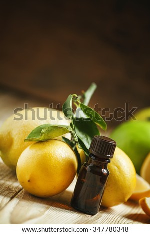 Essential oil of lemon and fresh lemons on the old wooden background, selective focus