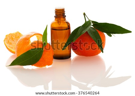 Essential oil of orange mandarin citrus fruit in little bottle decorated with mandarin peel, isolated over white background. - stock photo