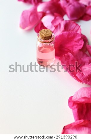 essential oil rose bottle spa pink petals vertical on white natural aroma perfume vial with cork feminine - stock photo