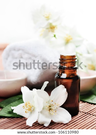 Essential oil with jasmine flower on wooden background