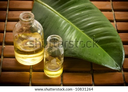 Essential oils and a green leaf on wooden tiles - stock photo
