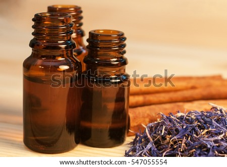 Essential oils in glass bottles, dried flowers and cinnamon sticks