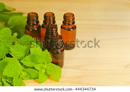 Essential oils in the glass brown bottles and mint leaves on the wooden background