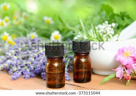 essential oils with herbs and mortar - stock photo