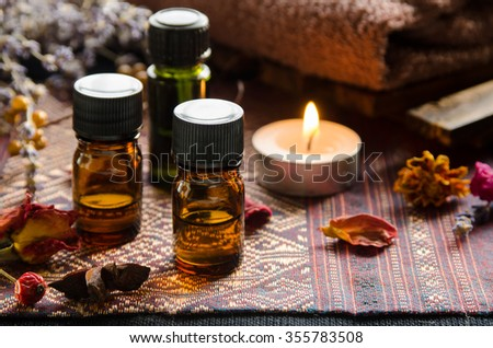 essential oils with herbs in candle light - stock photo