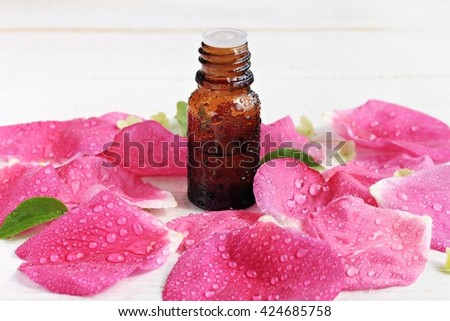 Essential rose oil bottle, pink fresh petals water-drops scattered, aromatherapy spa.  - stock photo