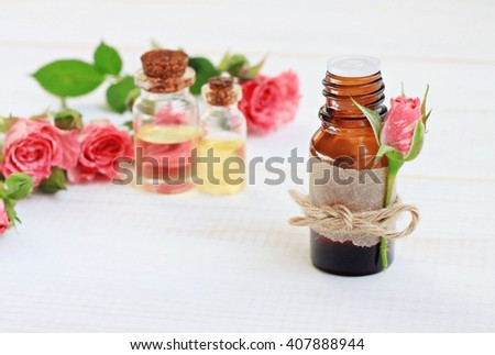 Essential rose oil in bottle, flower tied on label. Aromatic skin-beautifying treatment.   - stock photo