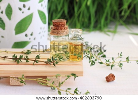 Essential thyme oil in bottles. Aroma lamp, fresh green herbs.	 - stock photo
