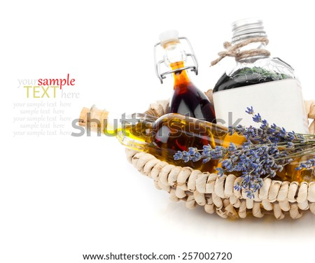 Essential various oils with lavender flowers, on white background. - stock photo