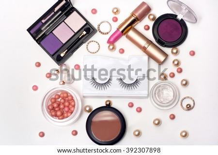Essentials for modern woman decorative cosmetics false eyelashes, powder, lipstick ,eye shadow white background. Top view  - stock photo
