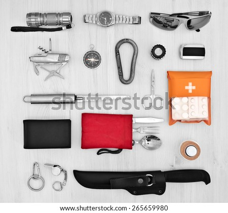 Essentials for the traveler, scout on a light wooden background. A set of tourist - stock photo