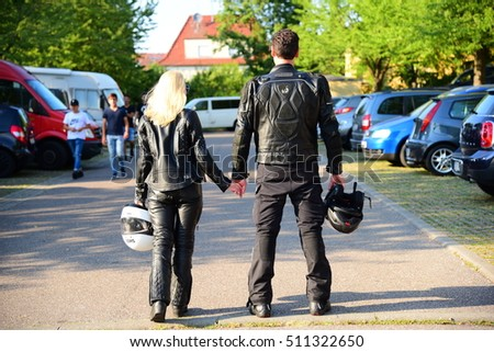 ESSLINGEN AM NECKAR, GERMANY - SEPTEMBER 11, 2016: Man and blonde woman in black motorsport outfit, from the back side, outdoor, Esslingen, Germany
