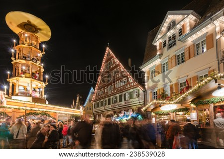 ESSLINGEN, GERMANY - DECEMBER 11, 2014: People are visiting the Christmas Market at night on December 11, 2014 in Esslingen, Germany. Long time exposure with blurred people. Esslingen at the river - stock photo