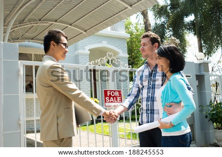 Estate agent and customer shaking their hands