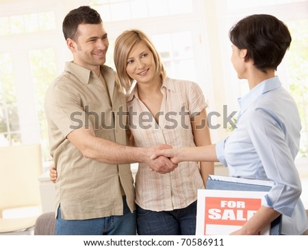 Estate agent congratulating young couple on making deal on new house.?