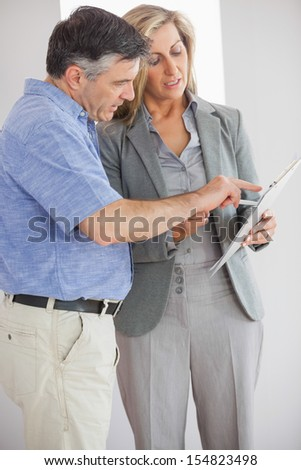 Estate agent explaining lease to customer in an empty home - stock photo
