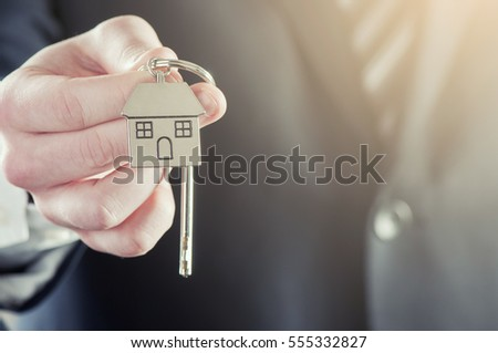 Estate agent giving house keys on a silver house shaped keychain