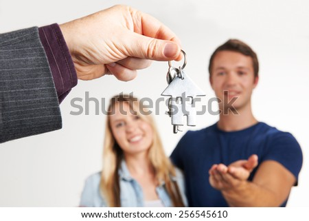 Estate Agent Handing Over House Keys To Young Couple - stock photo