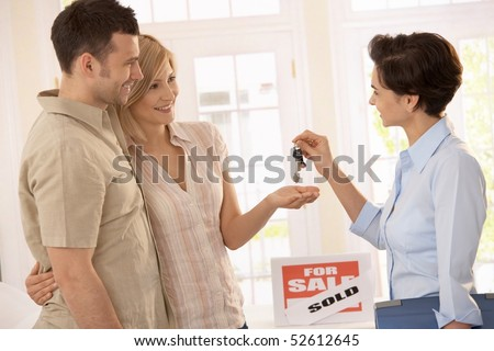 Estate agent handing over keys of new house to smiling couple. - stock photo