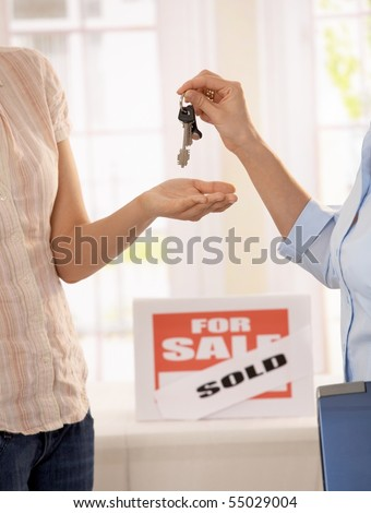 Estate agent handing over keys of new house to young owner. - stock photo
