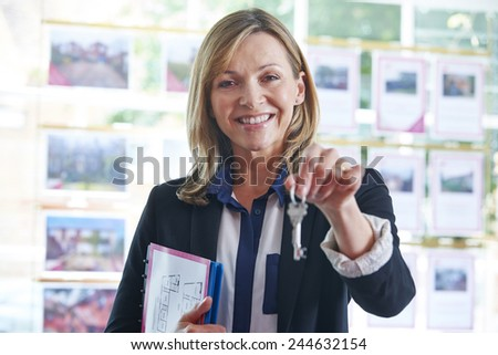 Estate Agent In Office Holding Keys To Property - stock photo