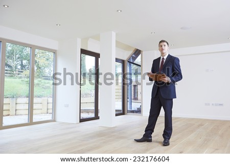 Estate Agent Looking Around Vacant Property For Valuation - stock photo