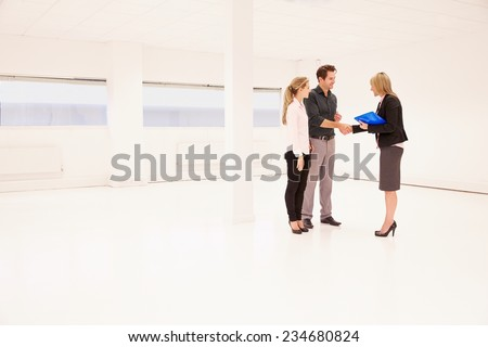 Estate Agent Shaking Hands With Clients In Empty Office - stock photo