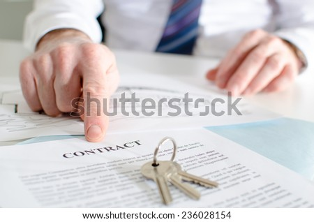 Estate agent showing a contract with his finger - stock photo