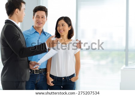 Estate agent showing house to the Asian family - stock photo