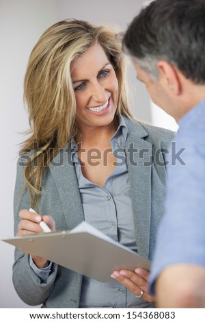 Estate agent showing lease to customer and smiling in an empty home