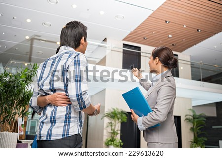Estate agent showing modern house to the couple - stock photo