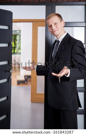 Estate agent stands at the entrance to the apartment and invites customers