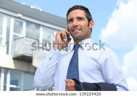 Estate agent stood outside property - stock photo