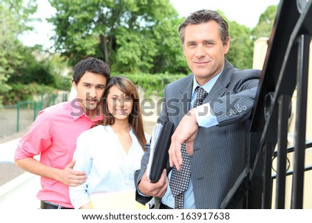 Estate agent with young couple - stock photo