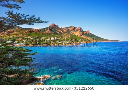 Esterel mediterranean red rocks coast, beach, tree and sea. French Riviera in Cote d Azur near Cannes Saint Raphael, Provence, France, Europe. - stock photo