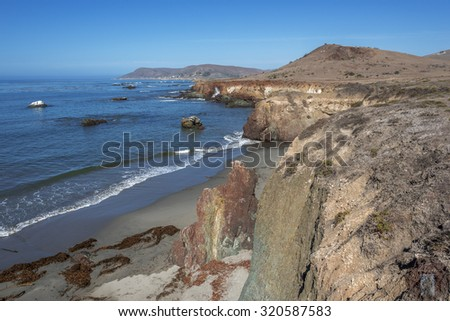Estero Bay/ Bluffs State Park, waves crashing / breaking on a sandy beach with huge colorful painted rocks, along the rugged Big Sur coastline, near Cambria, CA. on the California Central Coast.