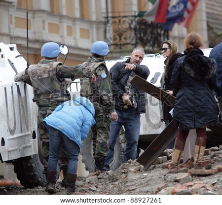 ESZTERGOM, HUNGARY - NOVEMBER 10: Angelina Jolie watches her bodyguard instruct actors playing peace keepers how to use a pistol on the set of In the Land Of Blood And Honey in Esztergom, Hungary, on Wednesday, November 10, 2010.