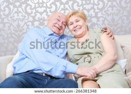 Eternal love. Affectionate happy retired couple with their heads together in a close embrace smiling at the camera - stock photo