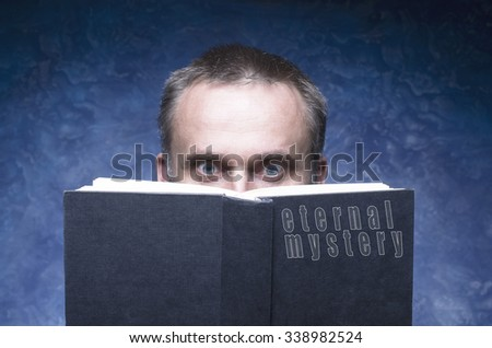 Eternal mystery written on the cover of the book, mature man being focused and hooked by book, reading open book, man behind book. - stock photo