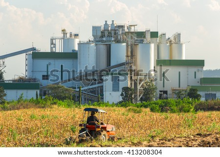 Ethanol industrial refinery with farm tractors in the foreground. - stock photo